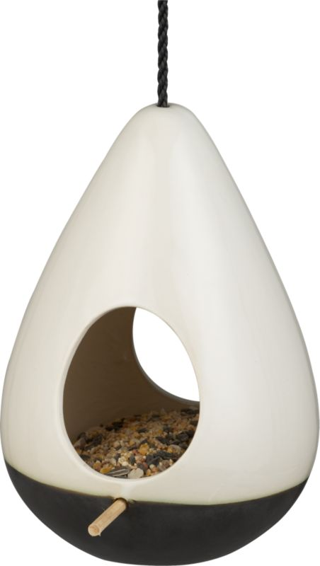 """<span class=""""copyHeader""""> tweet 'n' eat.</span> Teardrop habitat takes flight in off-white earthenware dipped below in brown reactive glaze. Two egg-shaped cutouts access wooden perch that's continuous side to side. Adjustable black rope suspends flight up to 16"""". Hang several at different heights for a fun flock.<br /><br /><NEWTAG/><ul><li>Off-white earthenware dipped in brown reactive glaze</li><li>For outdoor use</li><li>Clean with damp cloth</li></ul>"""