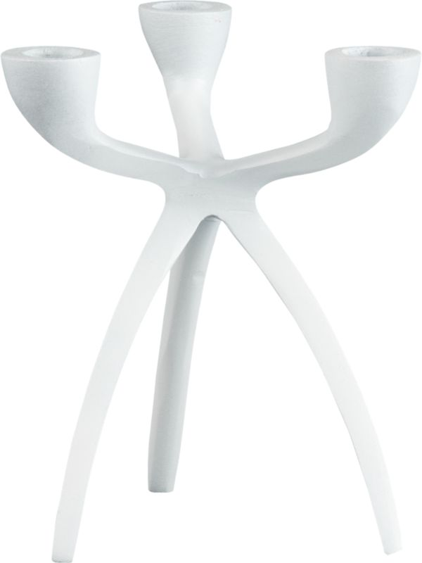 """<span class=""""copyHeader"""">glow with the flow.</span> Fluid sculpture stances graphic on bowed tripod legs that appear to be captured in motion. Handcast in white powdercoated aluminum, modern candleabra gives rise to three tapers—real flickers or our tric LED candle. Casts a striking glow with tri taper candleholder large black.<br /><br /><NEWTAG/><ul><li>Handcrafted</li><li>White powdercoated aluminum</li><li>Holds three taper candles</li></ul>"""