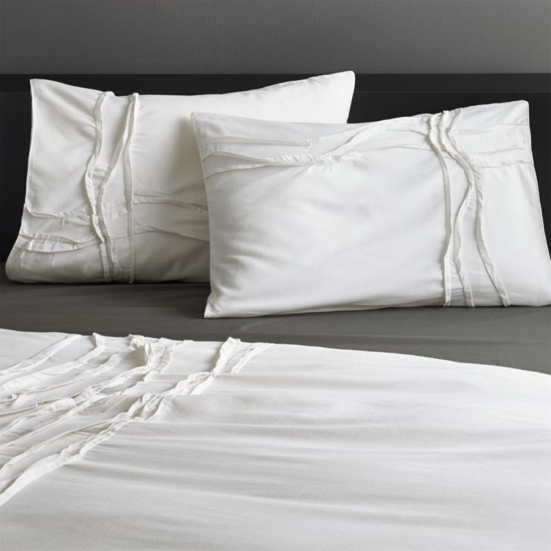 """<span class=""""copyHeader"""">monochromatic merge.</span> White-on-white sleepscape dreams up tone-on-tone texture. Woven of soft cotton/linen, flowing ribbons of fabric cross paths off-center in an organic ripple effect. Shams reverse to solid white. Shams are finished neat with envelope closures.<br /><br /><NEWTAG/><ul><li>Cotton/linen</li><li>250 thread count</li><li>Matching shams have envelope closure; reverse to solid white</li><li>Machine wash; line dry</li></ul>"""