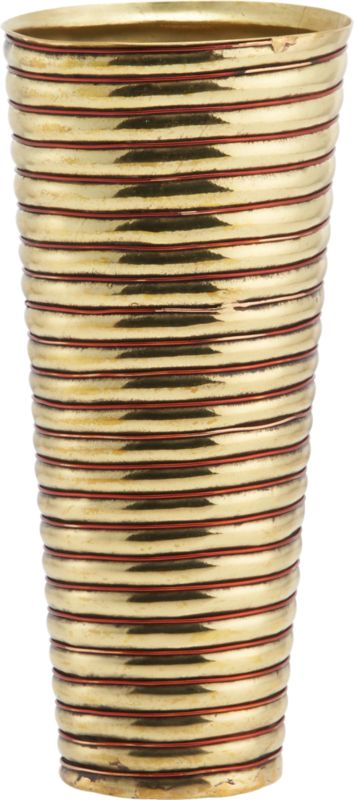 """<span class=""""copyHeader"""">brass rings.</span> Inspired by the coiled metal arm bands worn by the women of Rajasthan, India, this gleaming brass and copper wire vase reflects a cultural tradition. In this region, the quality and abundance of jewelry adorning the women from head to toe is indicative of a family's social status. Heated and hammered to form concentric rings, this vessel was handcrafted by traditional sheet metal artisans, known as thateras, in the small town of Rewari. Here on the outskirts of New Delhi, families have created decorative metalwork for centuries. Designer Neelima Rao observes: """"This piece keeps alive a visual vocabulary of craft.""""<br /><br /><span class=""""copyHeader"""">neelima rao.</span> Working primarily in metal and semi-precious stones, designer Neelima Rao creates objects that are a modern reflection of India's rich tradition of art and craft. """"The combination of the decorative Indian crafts when juxtaposed with the demands of modernity and simplicity often gives rise to unexpected and unique fusion pieces,"""" Rao says. Based in Faridabad, New Delhi, Rao finds inspiration in every village, town and city she travels to throughout India, each of which has its own craft or tradition of personal adornment or objects.<br /><br /><span class=""""copyHeader"""">CB2 Edition LMTD:</span> CB2 Edition LMTD original works are offered one time only in a small reserve. This special CB2 Edition LMTD design has a limited-edition release of 160.<br /><br /><NEWTAG/><ul><li>CB2 Edition LMTD design by Neelima Rao</li><li>Handcrafted of brass sheet metal with polished copper wire</li><li>Wipe with clean dry cloth</li></ul>"""