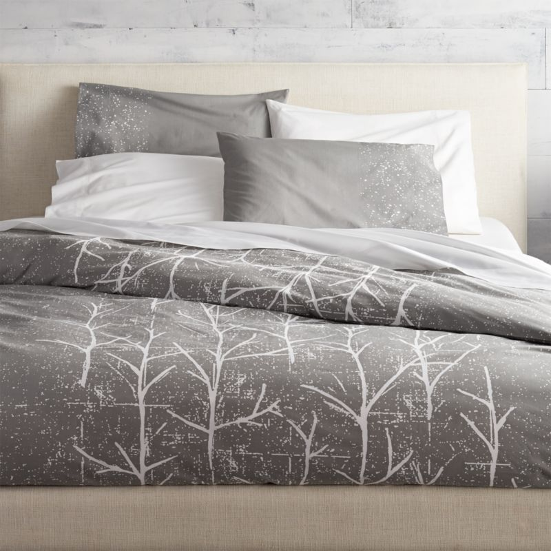 """<span class=""""copyHeader"""">branch out.</span> Painterly trees take root in a modern forest by Chicago-based designer Noël Ashby where white branches grow graphic on grey. Soft 200-thread-count cotton duvet cover has nonslip corner ties and hidden button closure; reverses to white. Dreamy with coordinating crumpled trees shams.<br /><br /><NEWTAG/><ul><li>Designed exclusively for CB2 by Noël Ashby</li><li>100% cotton</li><li>200 thread count</li><li>Duvet cover has non-slip corner ties and hidden button closure; reverses to white</li><li>Machine wash; do not dry clean</li></ul>"""