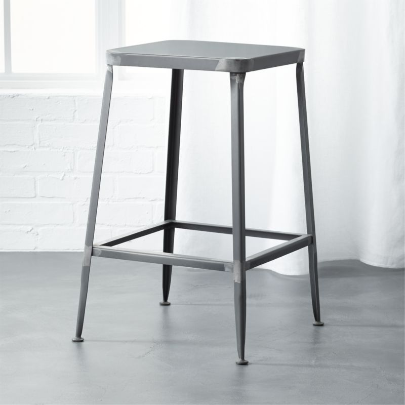 """<span class=""""copyHeader"""">quintessential.</span> Factory-inspired stool parks square at the bar in flint steel with raw metal finish, exposed welding. Legs flare refined, love those little capped feet. Each a handcrafted original.<br /><br /><NEWTAG/><ul><li>Handcrafted steel with raw finish</li><li>Flared legs</li><li>Feet have protective pads</li><li>24""""H seat sized for counters</li><li>Each is unique</li></ul>"""