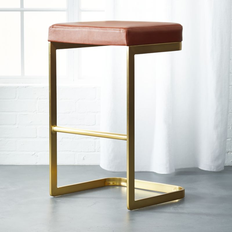 """<span class=""""copyHeader"""">box seat.</span>The Mack Leather Bar Stool was designed exclusively for CB2 in collaboration with Kravitz Design by Lenny Kravitz.<br />Glam yet functional, the stool is designed as a sleek study of contrasts observes Kravitz Design: """"It has a lightness, but doesn't look delicate...it's sophisticated, but comfortable...it's sexy, but very utilitarian."""" Thoughtfully engineered, Mack floats on a continuous cantilevered curve of brushed brass-plated metal, rising to a buttery saddle brown leather seat proportioned extra wide and deep for comfort. The mix of materials allows it to feel at home in both urban and rustic environments.<br /><br /><NEWTAG/><ul><li>Designed exclusively for CB2 by Kravitz Design</li><li>Base: Brass-plated metal tube</li><li>Seat: Saddle brown leather over poly foam pad</li><li>Wipe with soft, damp cloth; wipe spills immediately</li><li>For indoor use only</li><li>Assembly required; all hardware included</li><li>See product label or call customer service at 800.606.6252 for additional details on product content</li></ul><br />"""