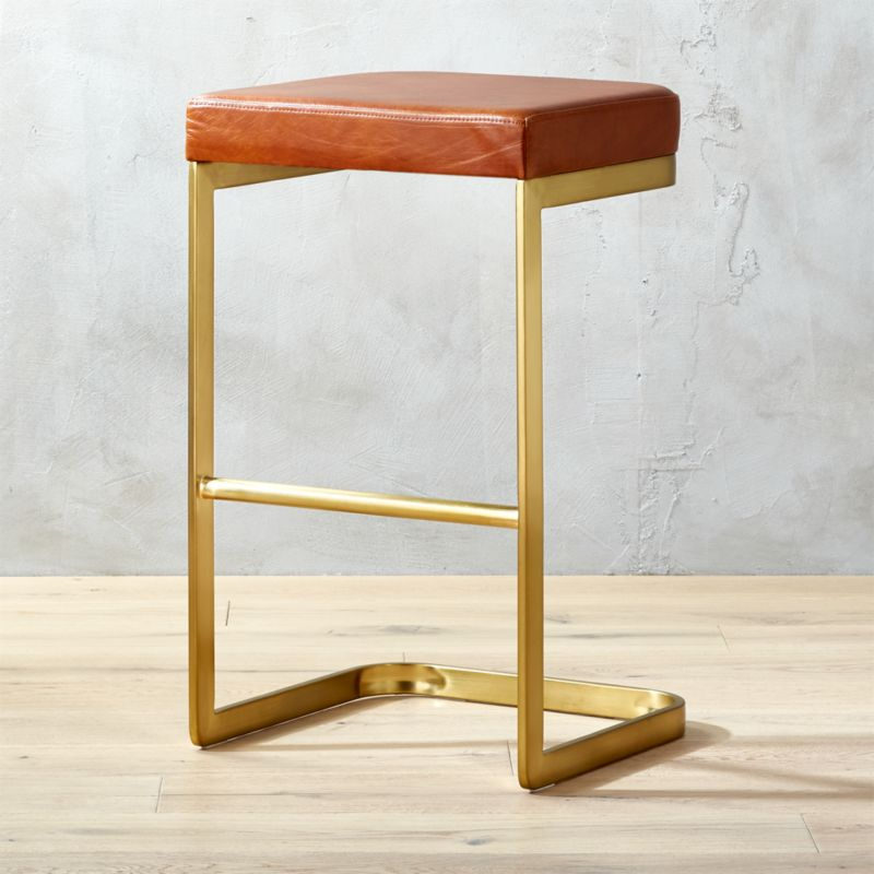 "<span class=""copyHeader"">Hot seat.</span> The Mack Leather Bar Stool was designed exclusively for CB2 in collaboration with Kravitz Design by Lenny Kravitz. Glam yet functional, the stool is designed as a sleek study of contrasts observes Kravitz Design: ""It has a lightness, but doesn't look delicate...it's sophisticated, but comfortable...it's sexy, but very utilitarian."" Thoughtfully engineered, Mack floats on a continuous cantilevered curve of brushed brass-plated metal, rising to a rich full-grain leather saddle brown seat proportioned extra wide and deep for comfort. The mix of materials allows it to feel at home in both urban and rustic environments.<br /><br /><NEWTAG/><ul><li>Designed exclusively for CB2 by Kravitz Design</li><li>Base: Brass-plated metal tube</li><li>Seat: Full-grain saddle leather</li><li>Wipe with soft, damp cloth; wipe spills immediately</li><li>For indoor use only</li><li>Assembly required</li></ul>"