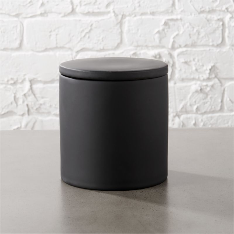 """<span class=""""copyHeader"""">noir side of neat.</span> Tactile stoneware round adds a modern touch with a surprising surface of black rubber. Fitted with a neat lid, canister stows cotton swabs and hair pins in the bath, paper clips and push pins in the office. Go for a full sensory experience with all of our rubber coated black accessories.<br /><br /><NEWTAG/><ul><li>Stoneware with black rubber coating</li><li>Glossy black interior</li><li>Hand wash</li></ul>"""