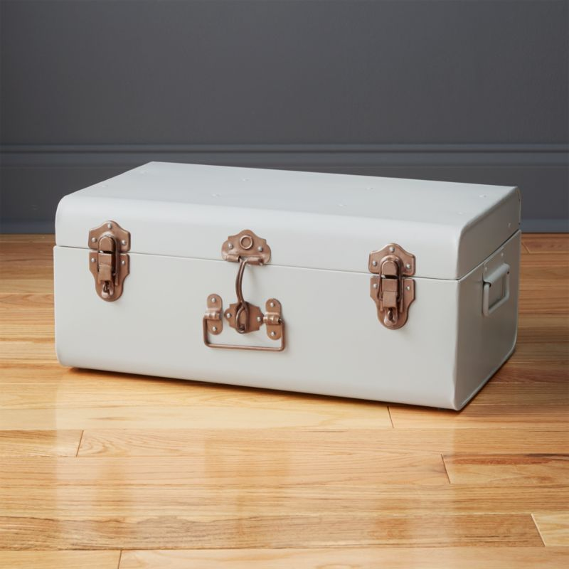 """<span class=""""copyHeader"""">bon voyage. </span> Grab your hat, white gloves and walking stick—old-world travel comes home in this vintage case made modern. 100% handmade, galvanized iron sheets are bent to shape then powdercoated for a matte white finish. Accented with authentic copper-plated front handle and latches, traveler throws back to a more elegant era. Stores everything from blankets to books to office supplies. Stack with large suitcase matte black for a sofa-side or bedside table.<br /><br /><NEWTAG/><ul><li>Handmade</li><li>Case: powdercoated iron</li><li>Front latches/handle: copper-plated iron</li><li>Plastic bumpers at bottom</li><li>Wipe with clean soft cloth</li></ul>"""