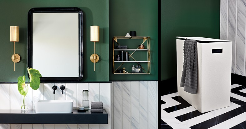 green bathroom. black mirror. white hamper. gold stool. gold wall sconce.